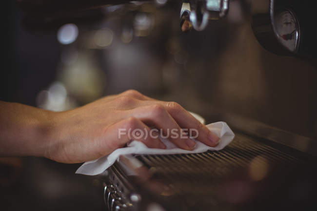 Close-up of waitress wiping espresso machine with napkin in cafe — Stock Photo