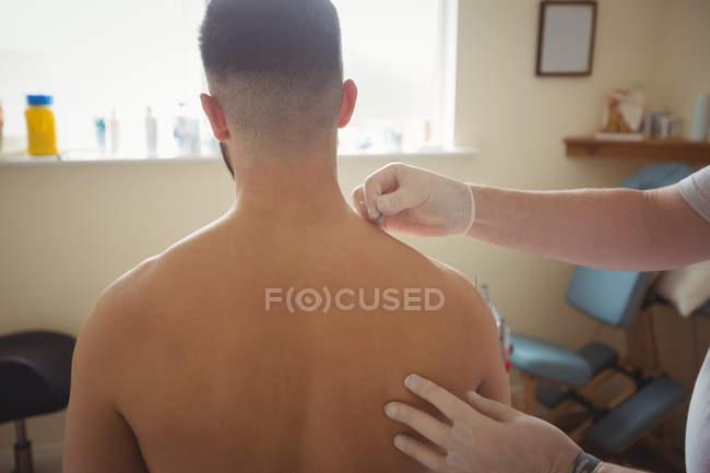 Fisioterapista che esegue l'ago secco sulla spalla del paziente in clinica — Foto stock