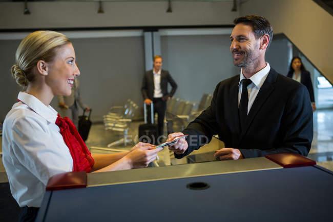 Funcionários do sexo femininos, dando o cartão de embarque ao empresário no check-in da mesa — Fotografia de Stock