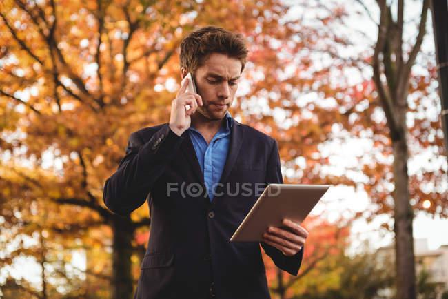 Empresário falando no celular e segurando tablet digital no outono — Fotografia de Stock