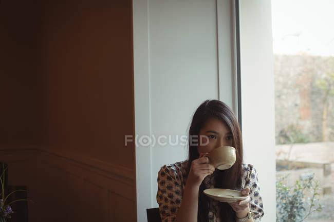 Beautiful woman having cup of coffee near window at cafe — Stock Photo