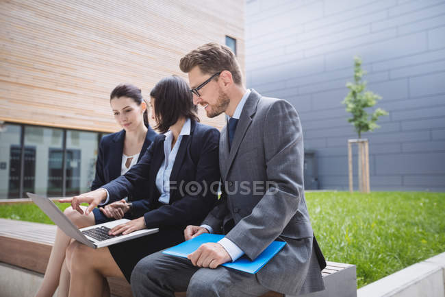Businesswoman sitting with colleagues and using laptop outside office building — Stock Photo
