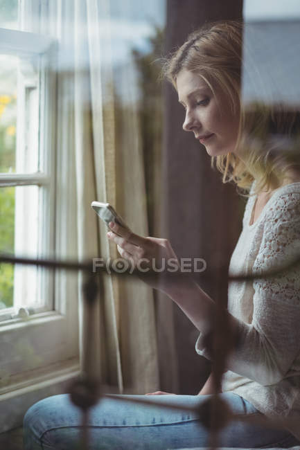 Beautiful woman sitting on bed and using mobile phone in bedroom at home — Stockfoto