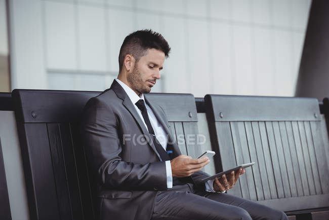 Businessman using digital tablet and mobile phone while sitting on a bench — Stock Photo