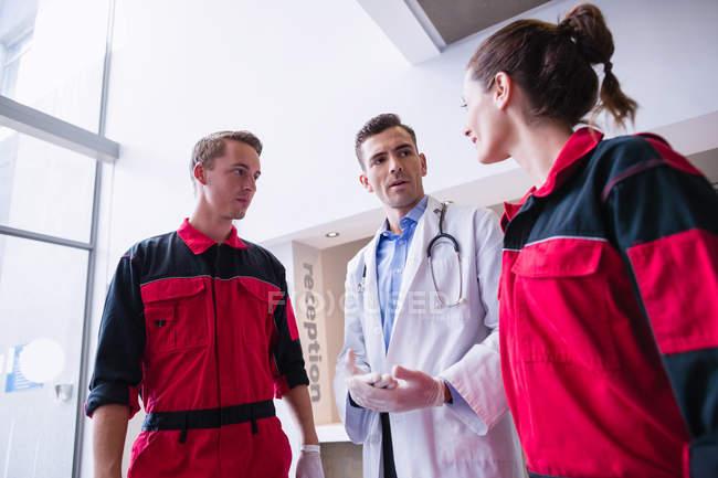 Médico falando com paramédico no corredor do hospital — Fotografia de Stock