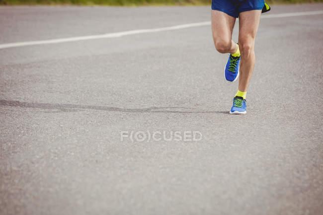 Низкая часть спортсмена бегает по дороге — стоковое фото