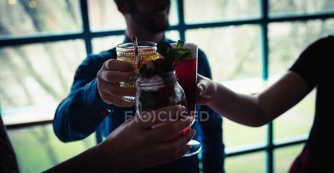 Three friends toasting glasses of drinks in bar — Stock Photo