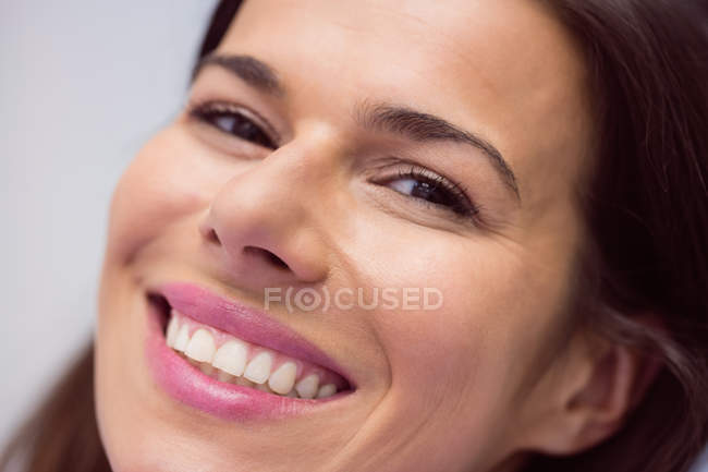 Close-up portrait of mid adult woman smiling and looking in camera — Stock Photo