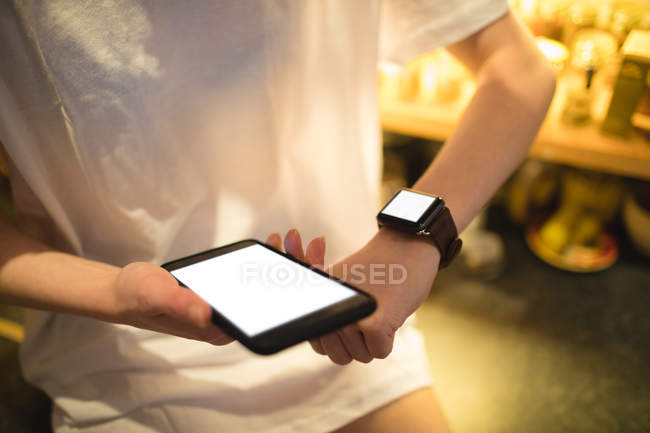 Mid-section of woman using smart watch while holding smartphone — Stock Photo