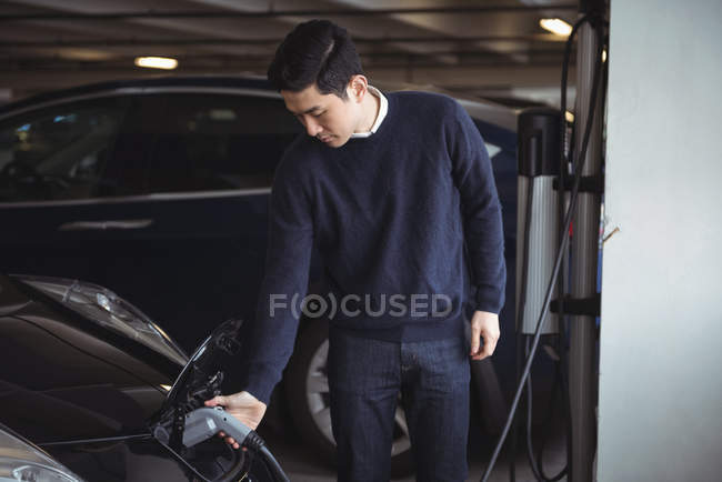 Handsome man charging car at electric vehicle charging station — Stock Photo