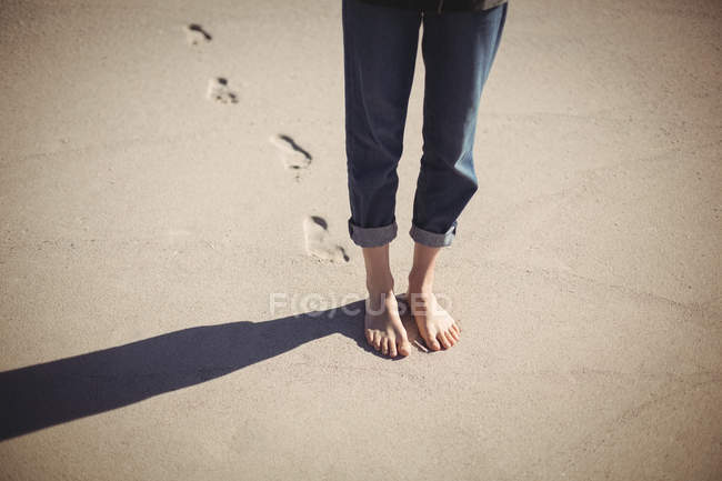 Low section of a woman walking on sandy beach — Stock Photo