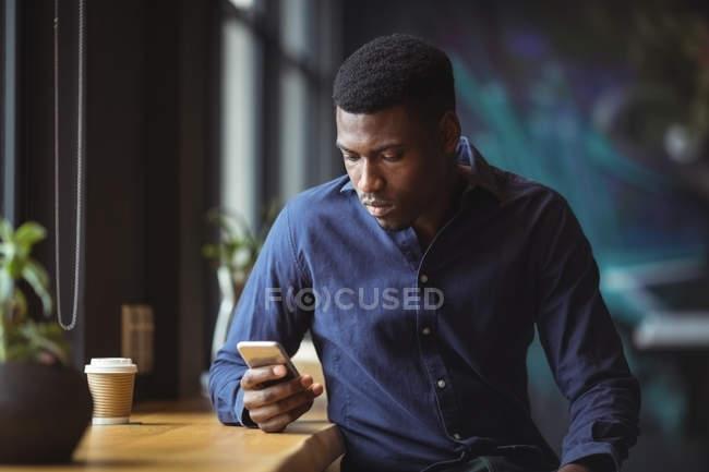 Homme d'affaires utilisant le téléphone portable dans le café de bureau — Photo de stock