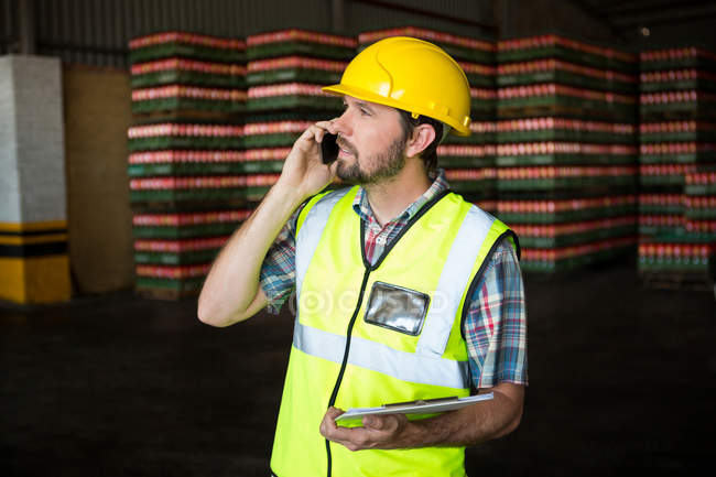 Male worker holding clipboard while talking on phone in factory — Stock Photo