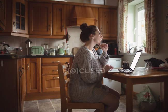 Femme réfléchie utilisant un ordinateur portable sur la table dans la cuisine à la maison — Photo de stock
