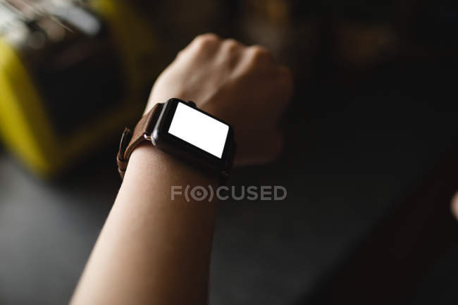 Close-up of woman wearing a smartwatch at home — Stock Photo