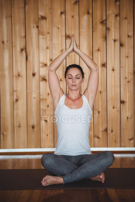 Healthy woman performing yoga in fitness studio — Stock Photo