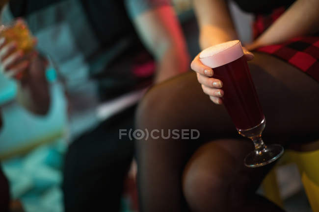 Woman holding a glass of drink in bar — Stock Photo