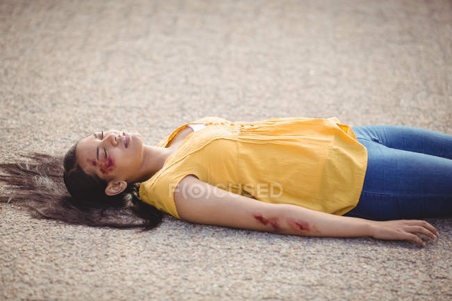 Close-up of unconscious woman fallen on ground after accident — стокове фото