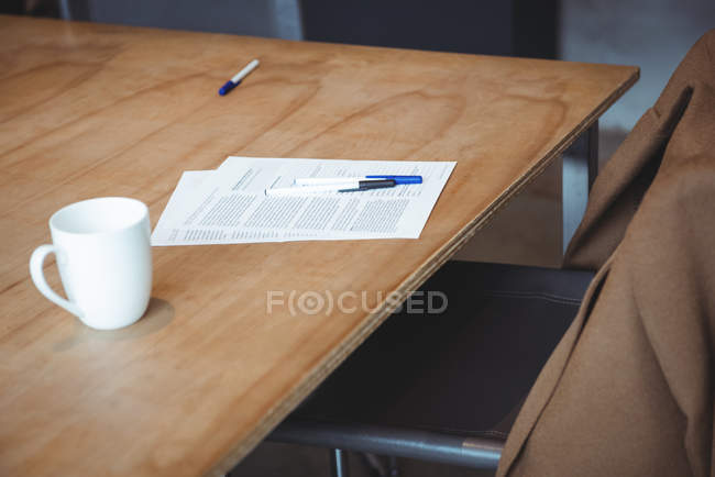 Tasse Kaffee und Dokument mit Stiften auf dem Tisch im Büro — Stockfoto