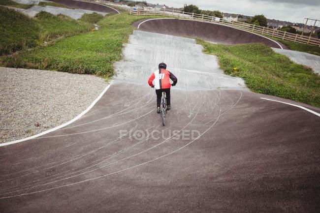 Vista trasera del ciclista montando en bicicleta BMX en skatepark - foto de stock