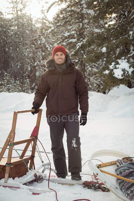 Musher maschio in piedi accanto alla slitta su un paesaggio innevato — Foto stock