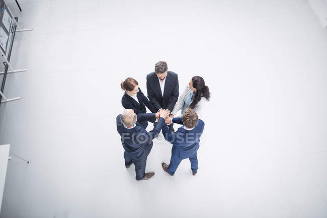 Overhead view of business people stacking hands together in office — Stock Photo