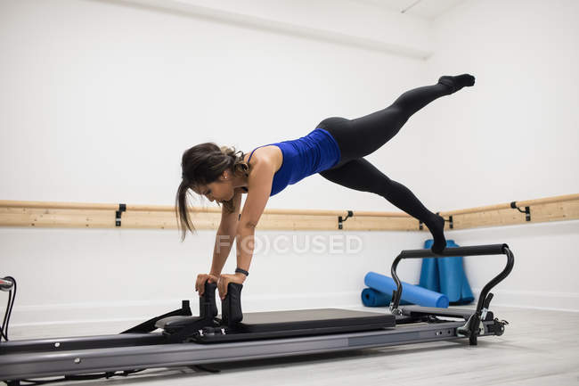 Mid adult woman stretching on reformer in gym — Stock Photo