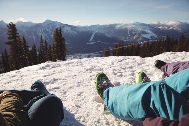 Low section of three skiers relaxing on snowy mountain during winter — Stock Photo