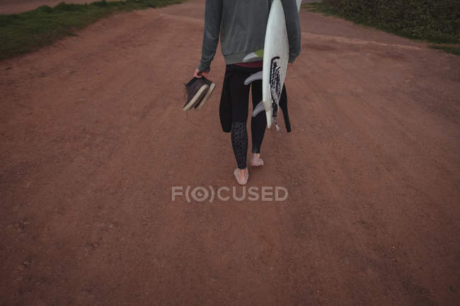 Low section of man carrying surfboard and shoes walking on road — Stock Photo