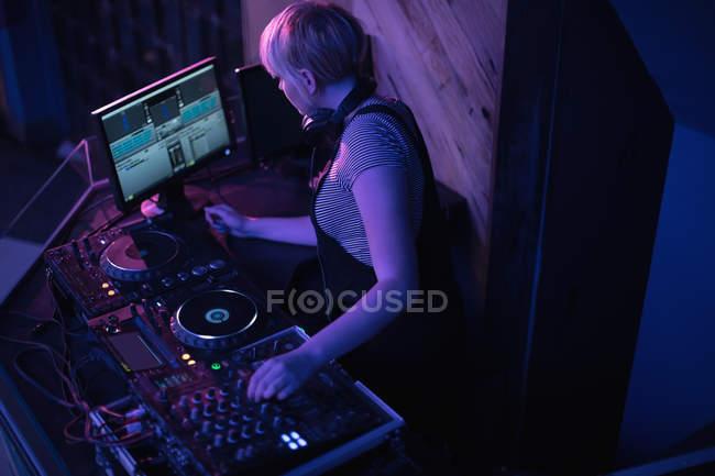 Femmina dj mixare musica su console di miscelazione in bar — Foto stock