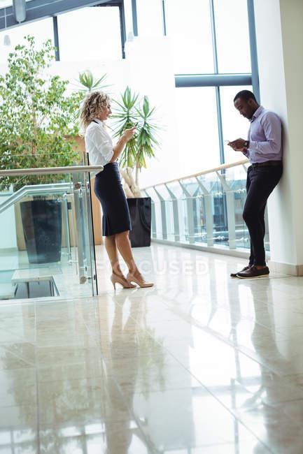 Dirigeants d'entreprises à l'aide de téléphones mobiles dans le couloir de bureau — Photo de stock