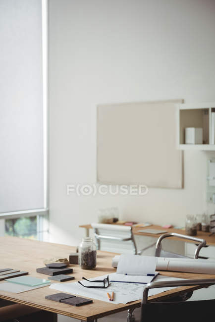 Stone slab, glass sheet and blueprint on table in office — Stock Photo