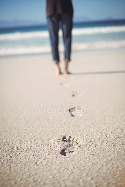 Close-up of footprints and low section of a woman walking on beach — Stock Photo