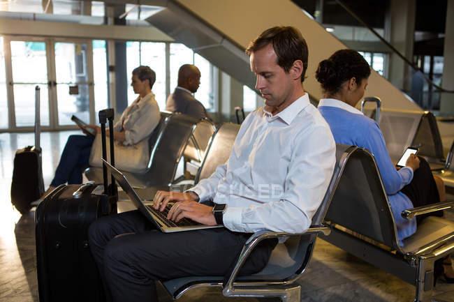 Человек с багажом с ноутбука в зоне ожидания в терминале аэропорта — стоковое фото