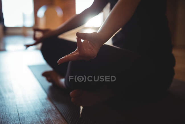 Cropped view of meditating woman doing mudra in yoga studio — Stock Photo