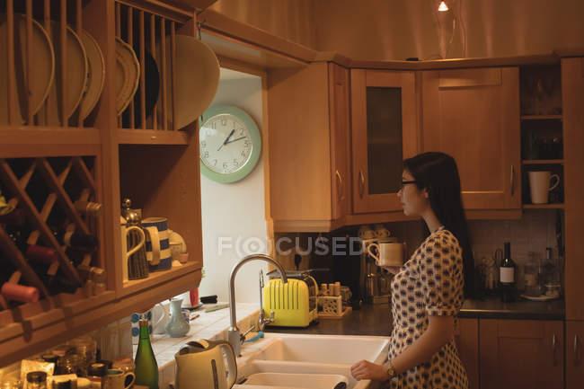 Mujer tomando café en la cocina en casa - foto de stock