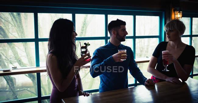 Tre amici che si godono un drink all'interno del bar — Foto stock