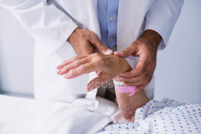 Doctor examining patients pulse in hospital room — Stock Photo