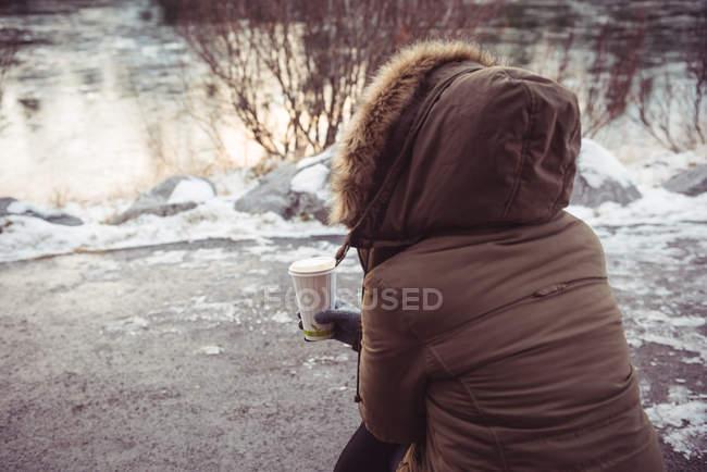 Вид сзади женщины, сидящей на берегу реки с одноразовой чашкой кофе зимой — стоковое фото