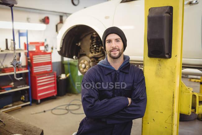 Портрет механік стоячи з руки пересічена в ремонт гаража — стокове фото