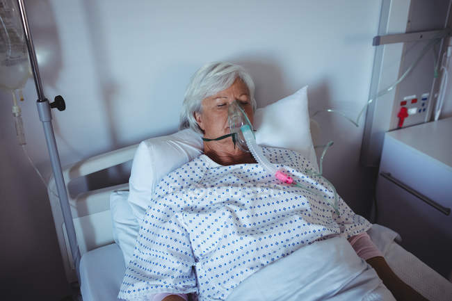 Senior patient lying on bed with oxygen mask on face in hospital — Stock Photo