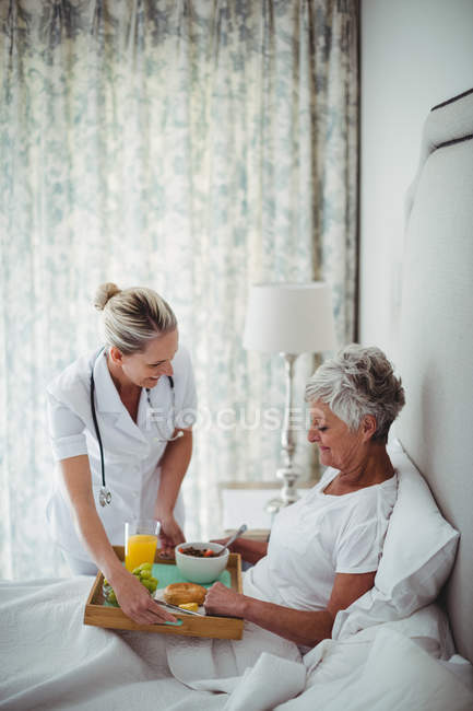 Врач, подающий завтрак пожилым пациентам в спальне — стоковое фото