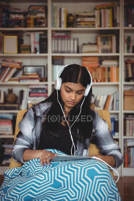 Donna che ascolta musica con cuffie e tablet digitale in salotto a casa — Foto stock