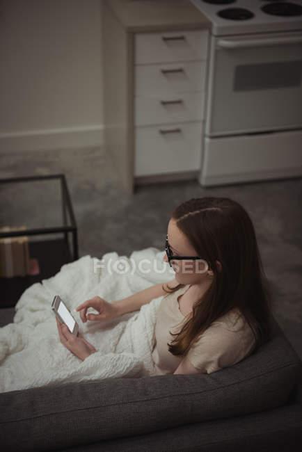 Donna che utilizza il telefono cellulare sul divano di casa — Foto stock