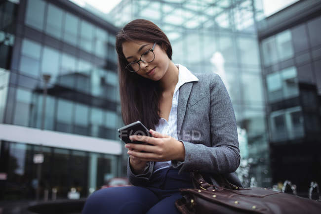 Businesswoman sitting near fountain and using mobile phone outside the office building — Stock Photo