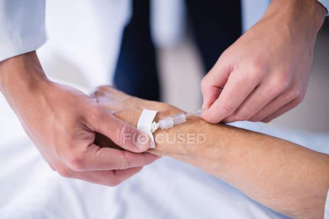 Arzt klebt Tropf auf Patientenhand im Krankenhaus — Stockfoto