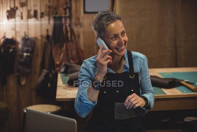 Parlare al cellulare in bottega artigiana artigiana — Foto stock