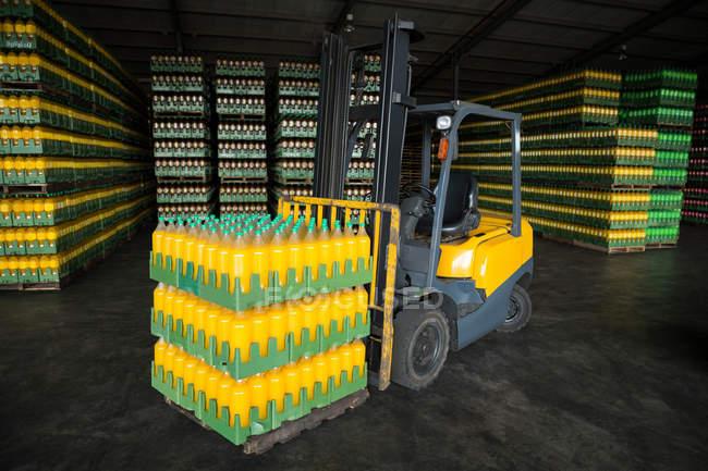 Impilabile di bottiglie di succo confezionato e carrello elevatore in magazzino — Foto stock