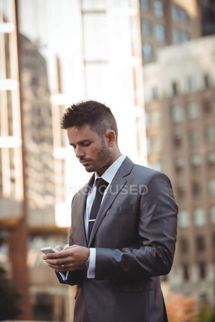 Businessman using mobile phone on urban street — Stock Photo