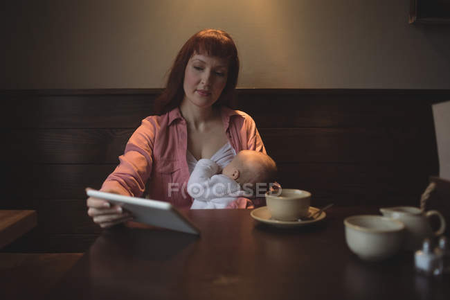 Mid adult woman with baby daughter using digital tablet in cafe — Stock Photo